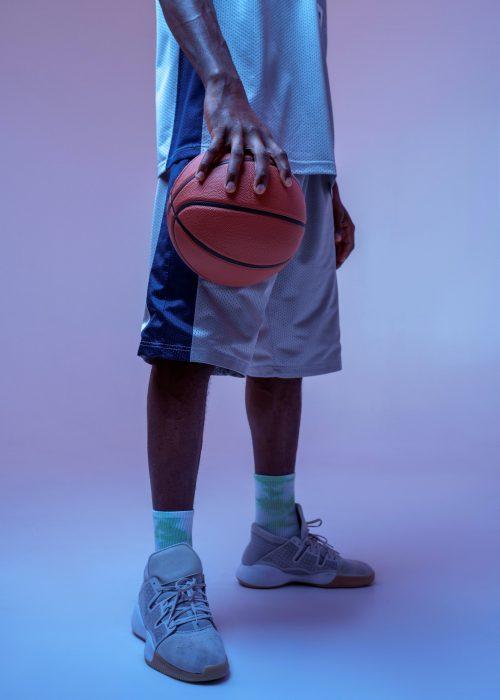 Strong basketball player hand holds ball